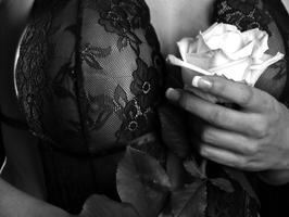 Erotikportrait einer Frau in Spitzenunterwäsche mit Rose in der Hand